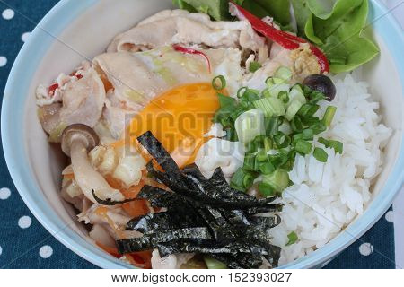 Close up of jasmine rice is topped soft boil eggs and fried pork in Japanese style  as
