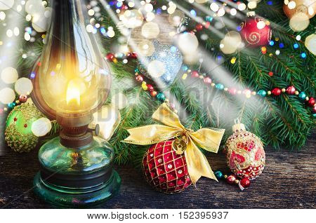 vintage burning lantern with decorated christmas evergreen wreath, low key with glimming lights