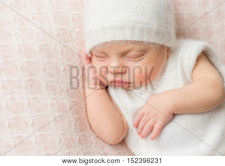 lovely sleeping newborn girl with sweet cheeks in white hat and suit