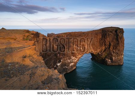 Beautiful summer landscape with rocky cape and ocean. Southern coast of Iceland. View of peninsula Dyrholaey, not far from the village . Art processing of photographs, color toning