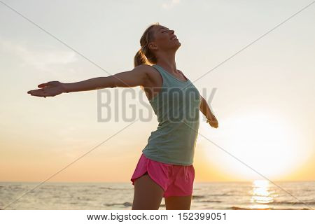 Happy woman on the beach with her hands extended
