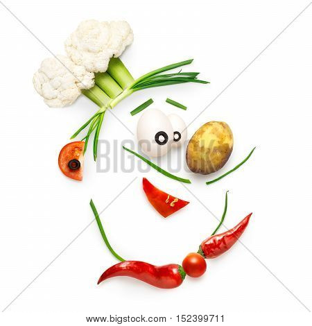 Creative food concept of a funny cartoon chef face made of vegetables isolated on white.