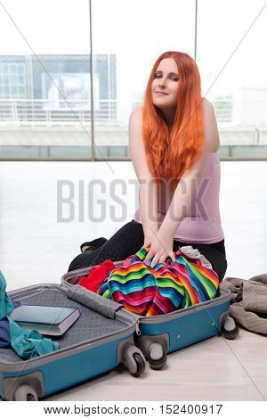 Young woman packing for travel vacation