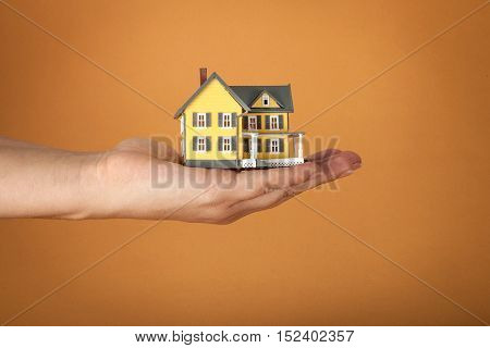 Men's Hand Holding a Model of a House on Orange Background