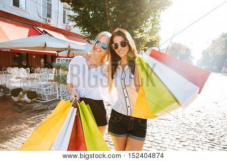 Two young fashion women with shopping bags walking along the street