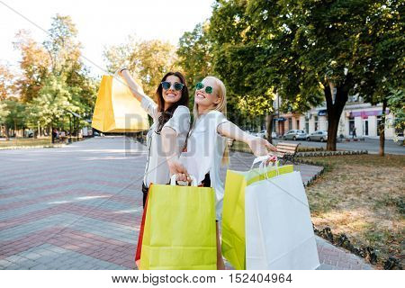 Two women shoppers in sunglasses holding shopping bags and walking in the city