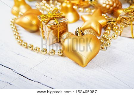 Brilliant gold baubles and cones like christmas decoration. Yellow balls ribbon gift bow heart and tinsel isolated on white background.