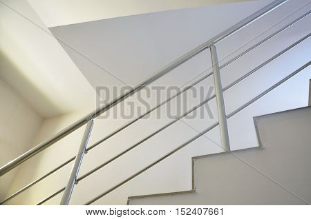 Detail of white modern staircase with metal guardrail. Look up.