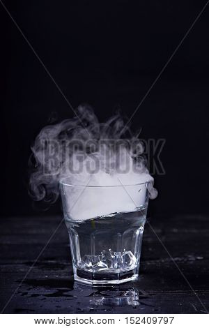 Hot water with a lot of steam in a glass at a black background. Dark photo. Concept photo: three state of water - ice, water, steam.