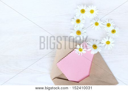 flat lay with an open letter to the paper flying off daisies outside view from above / idea messages from your heart