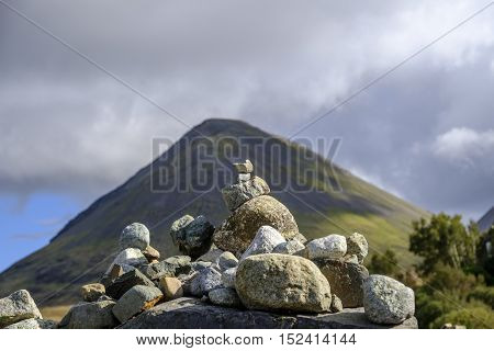 Focus on a small stone cairn of carefully balanced rocks in front of the beautiful landscape of Isle of Skye Scotland and the conical shape of Glamaig in the Red Hills mountain range.