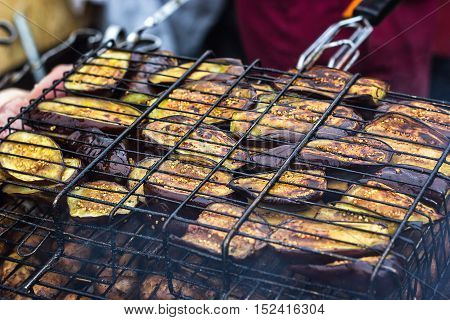 Fresh healthy eggplant or aubergine preparing on a barbecue grill over charcoal. Grilled aubergines eggplants slices. Vegetarian, Mediterranean cuisine. Delicious Food, vegetables on bbq party.