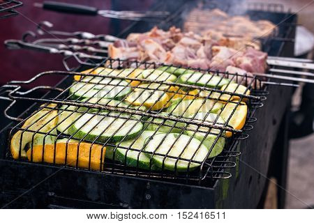 Fresh healthy green yellow zucchini courgettes cucumber preparing on barbecue grill over charcoal. Grilled zucchini slices. Vegetarian, Mediterranean cuisine. Delicious Food, vegetables on bbq party.