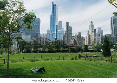Millennium Park Chicago USA - September 24 2015: Woman is reading a book in Millenium park. Millenium Park is one of the parks major attractions.