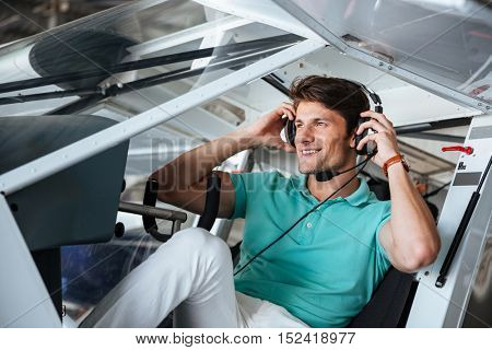 Smiling attractive young man pilot sitting in cabin of small aircraft