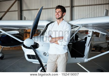 Cheerful young man standing with arms crossed near the plane