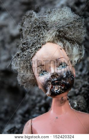 Melted face on scary girl doll on an ash background