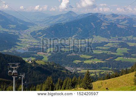KITZBUEHEL, AUSTRIA - SEPTEMBER 2016 : Kitzbuheler Hornbahn, Horn cable car traveling up down with view of valley, mountains of Kitzbuehel, Schwarzsee lake in Kitzbuhel, Austria on September 27, 2016