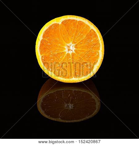 Orange slice isolated on a black glossy background with realistic reflection