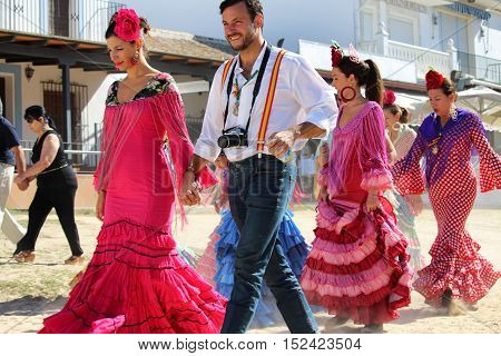 HUELVA/SPAIN - 9 OCTOBER 2016: Piligrims in colorful dresses going to the sunday holy mass at the shrine of El Rocio