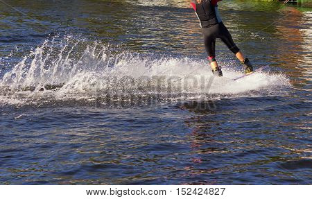 Sport. The wakeboarder on the water doing tricks. A lake in summer Sunny day.
