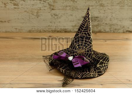 Small witch hat with golden spiderweb and a purple loopon a wooden background