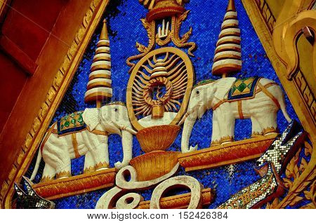 Phuket City Thailand - January 8 2011: Two carved elephant figures decorate the tympanum of a temple pavilion at Wat Mongkhol