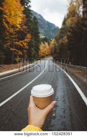 Drinking take away coffee on road. Fall trip. Rain weather. Freedom travel concept. Autumn weekend.