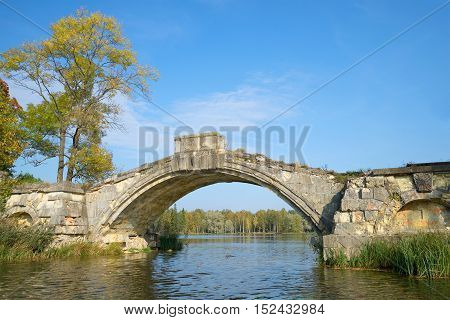 The remains of the old Humpback bridge on White lake. September in Gatchina Park, Russia