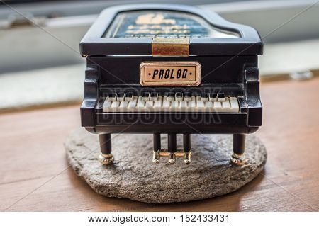Black piano music box on wooden background