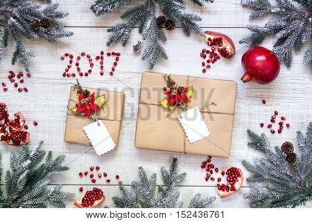 On the frame perimeter scattered branches of Christmas tree, pomegranates whole and broken, seeds, number 2017 and two gifts on white wood background. Gifts New Year's card background. Top view.