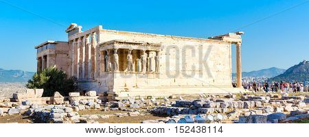Panoramic view with tourists taking photo near Erechtheum temple ruins decorated with Caryatids female statues in Acropolis