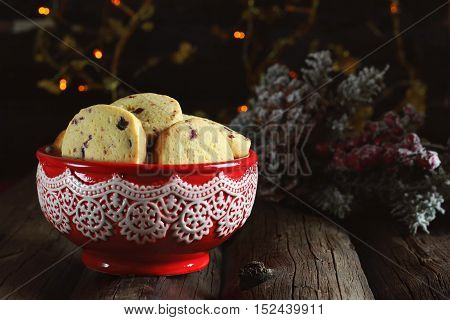 homemade cookies with a corn flour and dried cranberries in a red bowl on a wooden background