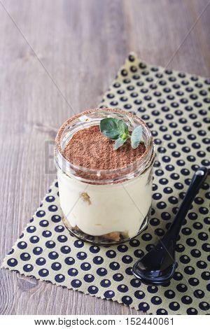 Traditional Italian Tiramisu dessert in mason jar on a wooden table