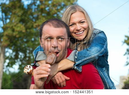 Woman embracing her man and eating ice cream and happy smiling. Close up of attractive mid adult couple eating ice cream and laughing in summer park outdoor.