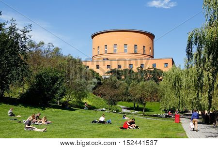 Stockholm, Sweden - August 6, 2015: The Stockholm public library located at street Sveavagen with park wit people sitting on the lawn in the foreground. Construction began 1924 and the library was opened in 1928. Architect was Gunnar Asplund.