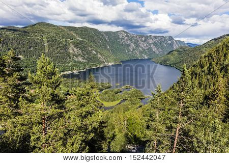 Dramatic clouds over mountains in a beautiful fjord in Telemark. Scenic landscape a summer day in Norway.