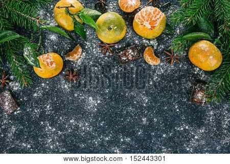 Top framework of mandarins with  evergreen twigs, star anise and chocolate over spotty black surface
