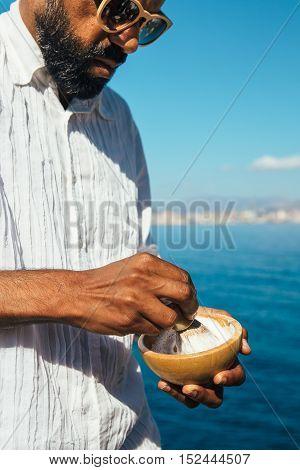Portrait of stylish bearded man in sunglasses dissolves foam with shaving brush
