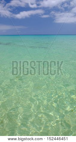 View on crystal emerald sea water with sand sea floor and blue sky with white clouds.