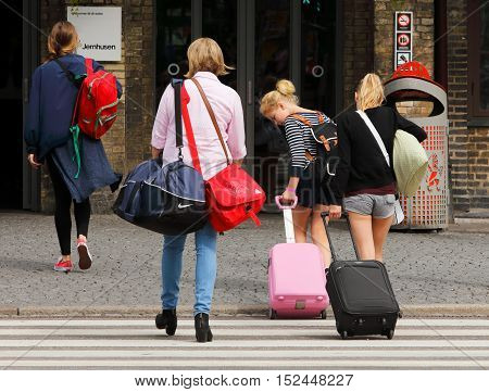 Gothenburg, Sweden - July 1, 2014: Four people with bags on their way to the railway station Centralstationen in Gothenburg.
