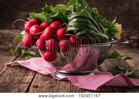 fresh vegetables in a metal colander healthy food on a wooden vintage table