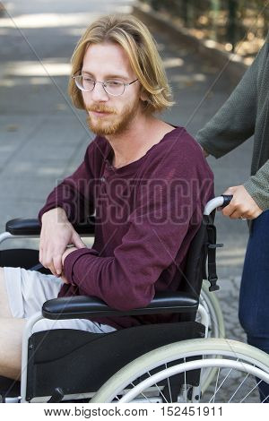 young man sitting in wheel chair and looking sad