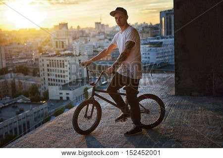 Bmx freestyler  Standing with his bmx on roof