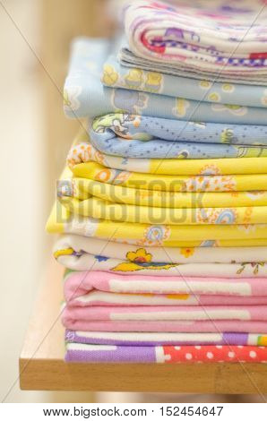 Stack of swaddling bands. Close-up of corner a laid colored laundry. Heap of folded linen of various colors. Pile of the washed and ironed linen.
