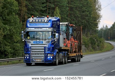 ORIVESI FINLAND - SEPTEMBER 1 2016: Customized blue and silver Scania semi V8 of PTA-Kuljetus hauls roadworks equipment along rural road in Finland.
