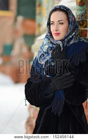 Portrait of beautiful  brunette girl in a blue scarf in the winter