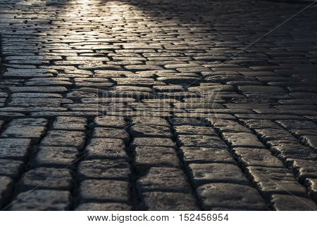 Black cobbled stone road background with reflection of light seen on the road. Black or dark grey stone pavement texture. light on the stone pavement