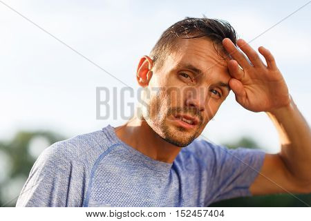 Athlete closeup bent head and wipes forehead with his fingers