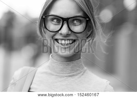 Portrait of smiling student on background of building, black - white photo